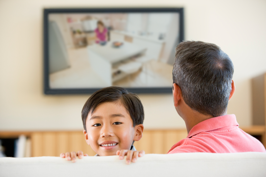 man and boy watching tv in living room