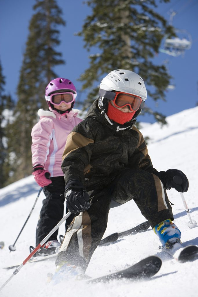 Children skiing downhill with helmets and goggles