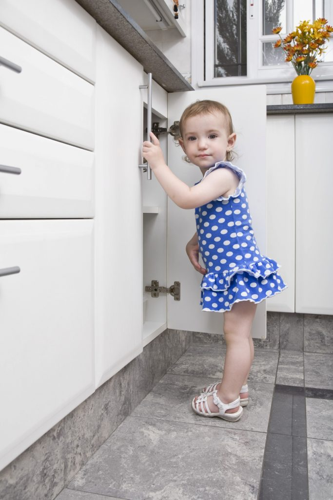 girl opening cupboard in kitchen