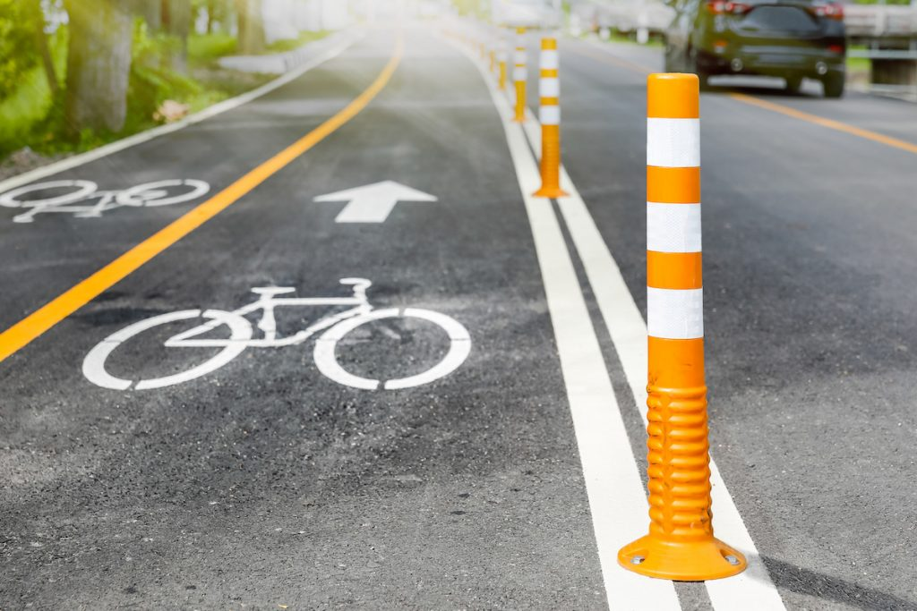 Close-up of a bike lane with orange bollards