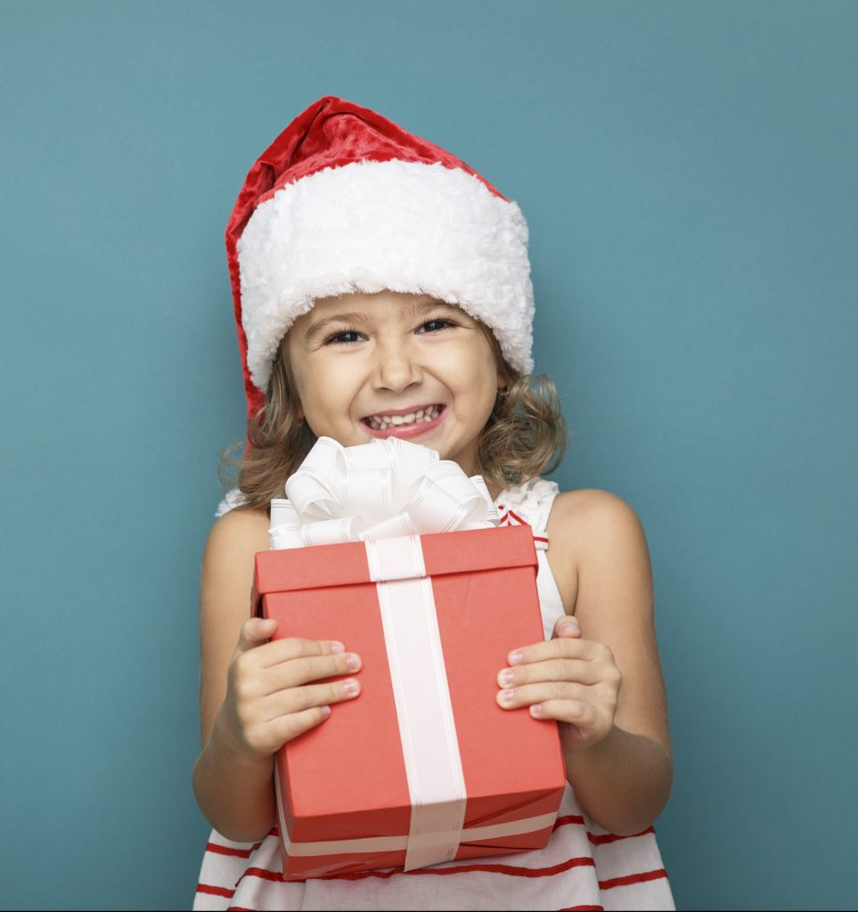 Close-up of a girl wearing a Santa hit and holding a red gift box
