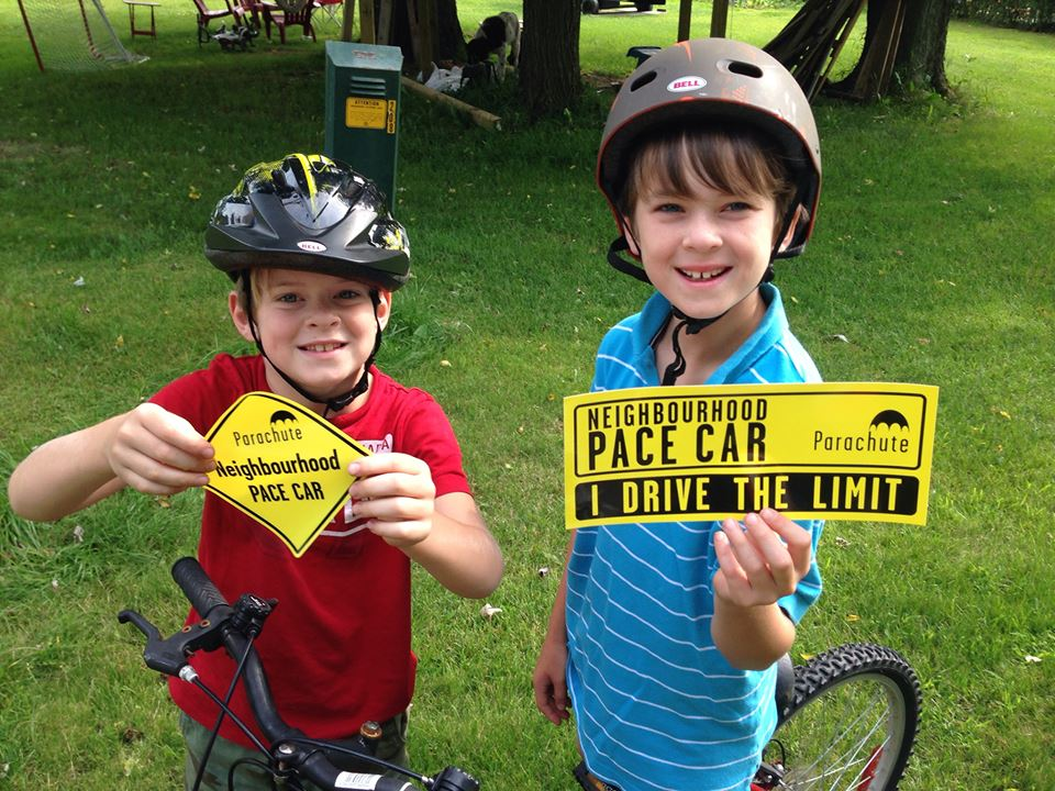 Two children wearing helmets holding Parachute Pace Car stickers