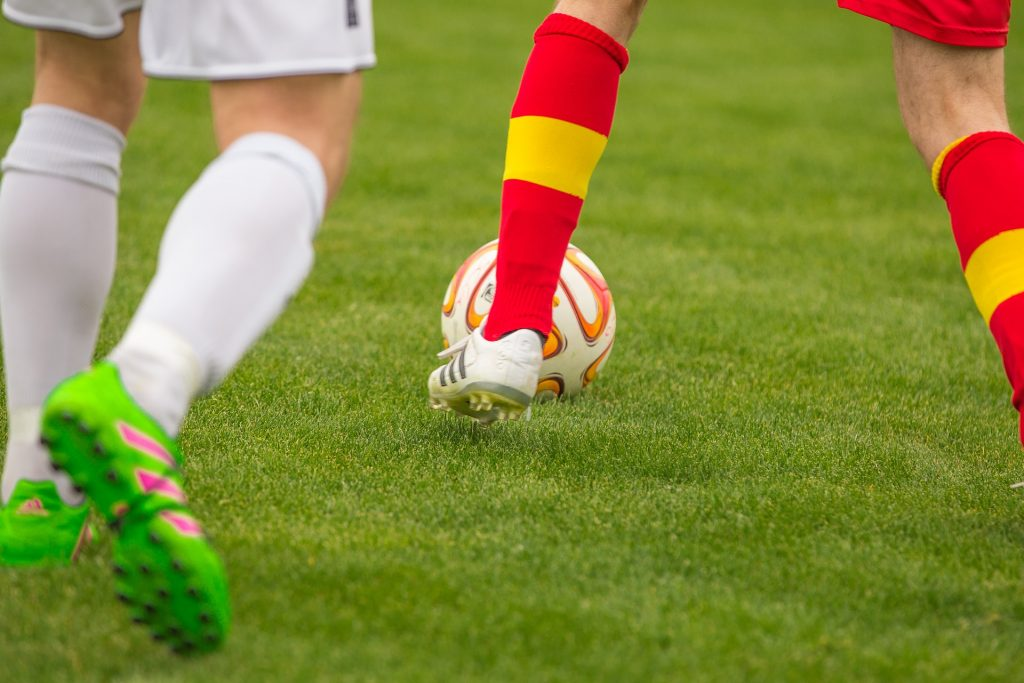 Close-up of someone dribbling a soccer ball wearing cleats
