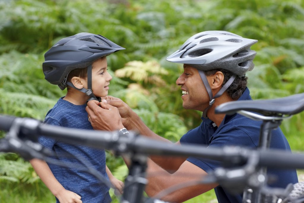 Man putting on a bike helmet for a child