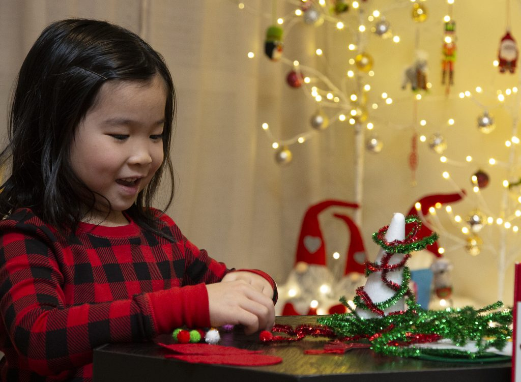 A girl in red plaid sweater playing with a toy at a table with Christmas lights in background.